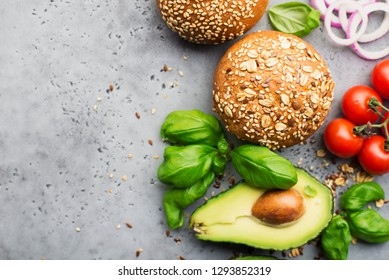 Healthy food. Veggie burger ingredients cereal buns, avocado, cherry tomatoes, basil, sweet onions on a light gray background. Top view, space