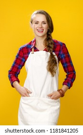 Healthy food to your table. happy young woman farmer wearing apron isolated on yellow