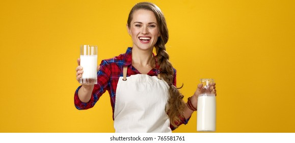 Healthy food to your table. Portrait of smiling modern woman cook wearing apron isolated on yellow background giving glass of homemade fresh raw milk