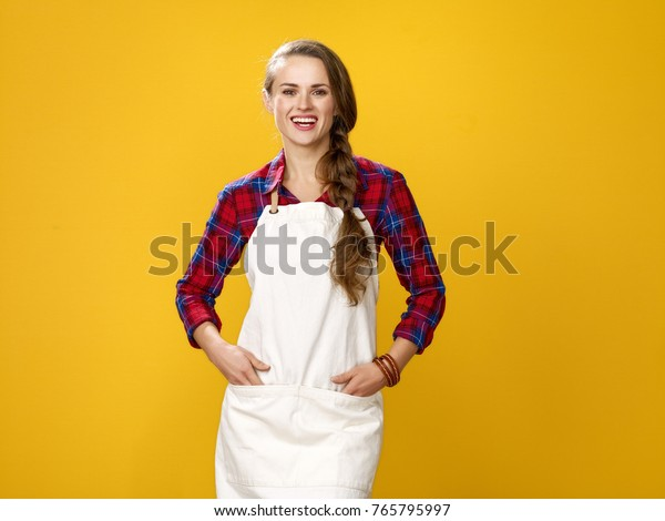 Healthy food to your table. Portrait of happy young woman farmer wearing apron isolated on yellow