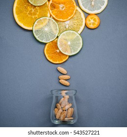 Healthy foods and medicine concept. Bottle of vitamin C and various citrus fruits. Mixed citrus fruits sliced lime,orange and lemon on gray background flat lay.