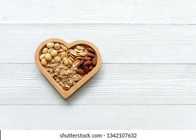 Healthy Foods. Mixed nuts in heart shape with nuts for diet on white wood. Different kinds of tasty and healthy nuts. Top view and copy space.  Healthy Concept