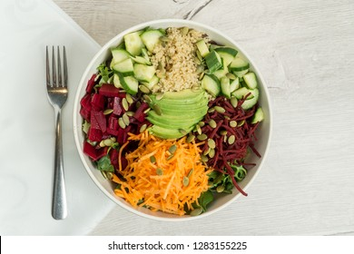 Healthy fresh bowl salad with spinach, pickled raw beets, carrots cucumber, quinoa, avocado, pumpkin seeds and green goddess vinaigrette dressing