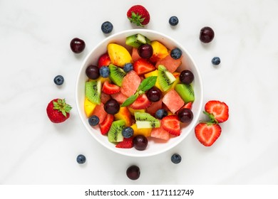 healthy fresh fruit and berry salad with mint in a bowl on white marble background. healthy food. top view.