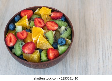 Healthy fresh fruit salad in bowl on light background.