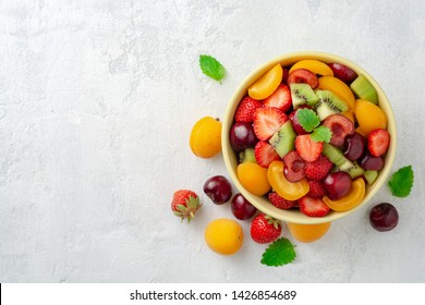 Healthy fresh fruit salad in bowl on gray concrete background. Top view. Copy space.