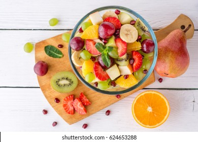 Healthy fresh fruit salad in glass bowl on white wooden background. Top view.