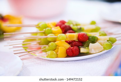 Healthy fresh fruits in a plate .Mixed fruits  on skewers isolated on white background
