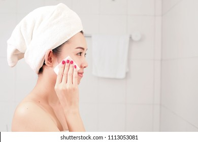 Healthy fresh girl removing makeup from her face with cotton pad.