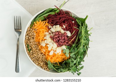 Healthy fresh Glory bowl salad with farro, brown rice, spinach, carrot, beets, pea shoots, almonds, pomegranate seeds and tahini glory dressing