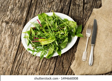 Healthy fresh green salad leaves on plate with cutlery on rustic wooden background.