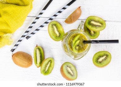 Healthy fresh kiwi smoothie in glass on a wooden background. Focus on kiwi slice in a carafe.