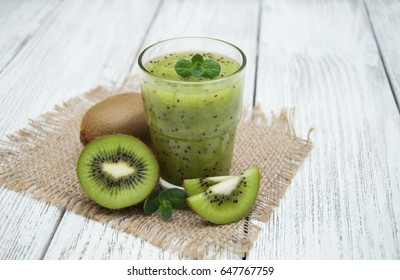 Healthy fresh kiwi smoothie in glass on a wooden background
