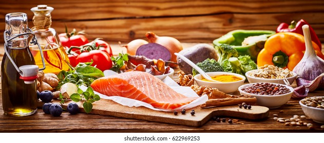 Healthy fresh raw food for the heart in a banner format on rustic wood with salmon, assorted spices, herbs, nuts, peppers, blueberries, tomato, onion, broccoli, garlic, soy sauce and olive oil