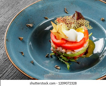 Healthy fresh salad with avocado, tiger prawns, capers, tomato, poached egg in plate over dark table. Healthy vegan food, clean eating, top view