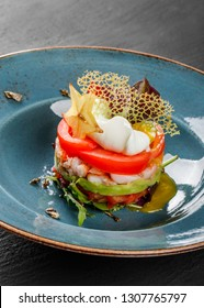 Healthy fresh salad with avocado, tiger prawns, capers, tomato, poached egg in plate over dark table. Healthy vegan food, clean eating