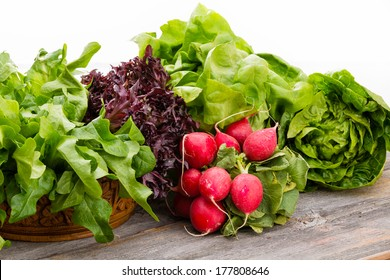Healthy fresh salad ingredients displayed on old weathered wooden boards with several varieties of leafy green lettuce and a bunch of crisp peppery radish over a white background with copy space
