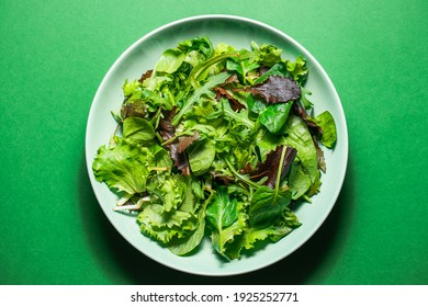 Healthy fresh salad of spinach, arugula, mini romaine lettuce, batavia salad in a green plate on a green background. Food background for menu, recipe. Top view. salat with green leafs - Shutterstock ID 1925252771