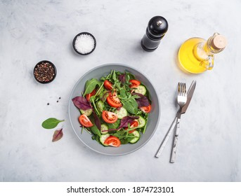 Healthy fresh salad of vegetable cucumber, tomato, spinach, arugula in plate on stone grey table. Food background for menu, recipe. Top view - Shutterstock ID 1874723101