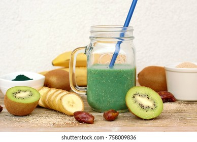 Healthy fresh smoothie drink from banan,kiwi,poppy seed and spirulin in glass on wooden background, front horizontal view