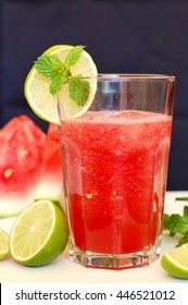 Healthy fresh smoothie drink from red watermelon, lime, mint and ice drift in glass, front vertical view