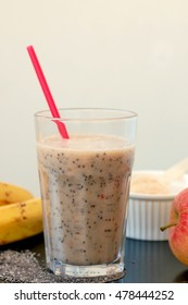 Healthy fresh smoothie drink from red apple, banana chia seeds and plant protein powder in the glass with straw, front vertical view