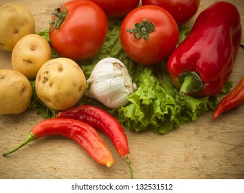 Healthy fresh vegetables ingredients for cooking in rustic setting: tomatoes, garlic, spices, chili. pepper