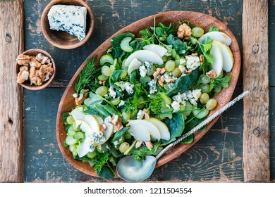 Healthy fresh vegetarian apple green salad with celery, walnuts, grapes and honey