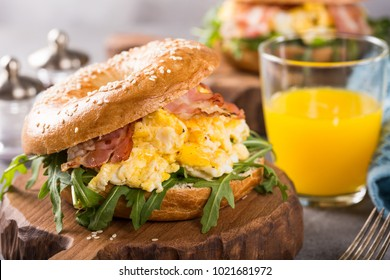 Healthy freshly baked bagel filled with scrambled eggs, rucola and fried bacon. Served on small wooden cutting board on gray background. Breakfast food.
