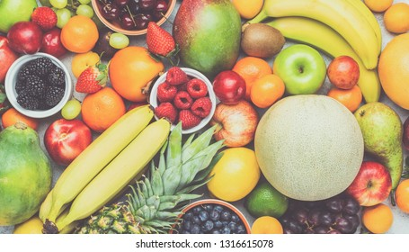 Healthy fruit background filled with strawberries raspberries oranges plums apples kiwis grapes blueberries mango persimmon pineapple, toned, selective focus