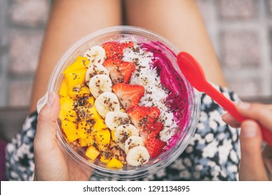 Healthy fruit breakfast pitaya bowl. Girl eating fruits smoothie sitting outside in park for lunch break. vegan food closeup. Dragonfruit puree, bananas, strawberries, mangos, coconut, flax seeds.
