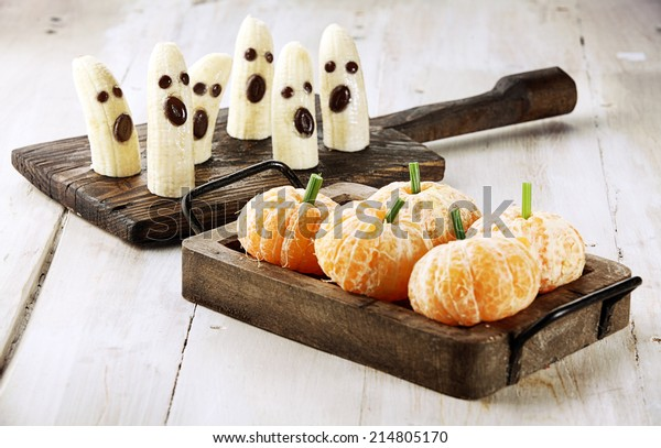 Healthy Fruit Halloween Treats made into Banana Ghosts and Clementine Orange Pumpkins