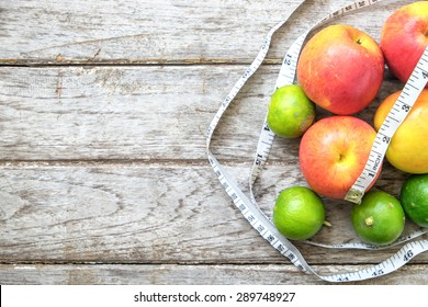 Healthy Fruit with measuring tape on wooden top , for lose weight ,Diet , still life background, Healthy lifestyle concept