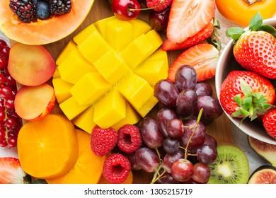 Healthy fruit platter background, strawberries raspberries oranges plums apples kiwis grapes blueberries mango persimmon, top view, selective focus