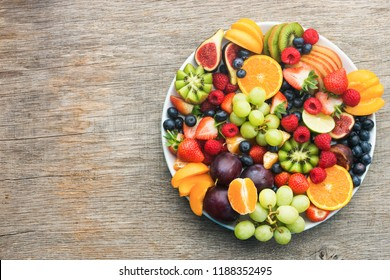 Healthy fruit platter, strawberries raspberries oranges plums apples kiwis grapes blueberries on the dark grey wooden table, top view, copy space for text, selective focus