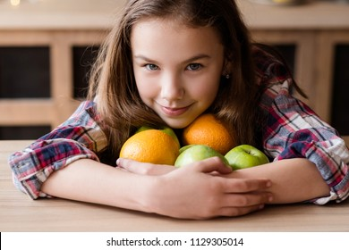 healthy fruit snacks for kids. wholesome diet and natural organic food for children development. girl holding a mix of oranges and apples in hands
