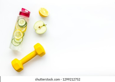 Healthy fruit water for sport, fitness. Bottle of water with lemon and cucumber near sport equipment dumbbells on white background top view space for text