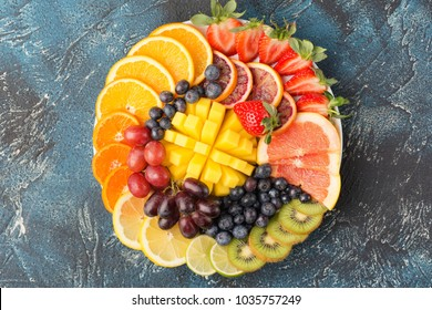Healthy fruits and berries platter in rainbow colours, strawberries, mango, grapes, oranges, kiwis, lemons on the blue table, copy space for text, selective focus