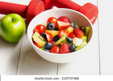Healthy Fruits. Fresh fruits salad diet slim fit with dumbbells sport equipment, water and banana for healthy lifestyle women. Weight Loss and Diet Concept.  select focus