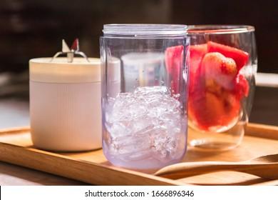Gesunde Früchte mit tragbarem Mixer auf hölzernem Tablett, der sich für die Herstellung eines Smoothies vorbereitet. frische Erdbeere und Wassermelone mit Eis; gesundes und frisches Konzept.