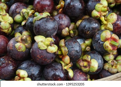 Healthy fruits Red mangosteen background, dark mangosteen, dark mangosteen in a supermarket local market bunch of mangosteen ready to eat.Fresh mangoteen in market. / mangoteen background.
