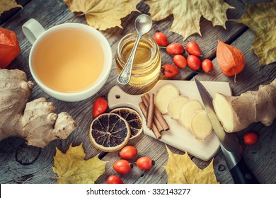 Healthy ginger tea, jar of honey, ginger root, dried lemon slice, wild briar and cinnamon on table with autumn maple leaves. Top view.