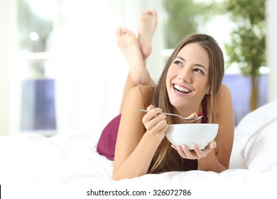 Healthy girl eating cereals at breakfast lying on the bed at home or hotel