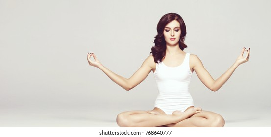 Healthy girl meditating in lotus position. Yoga, zen, Buddhism, recovery and wellbeing concept.