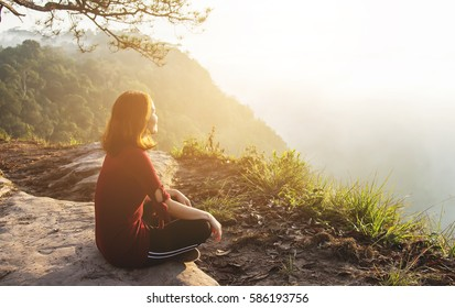 Healthy girl relaxing on mountain with sunlight flaring in tropical forest, healthcare lifestyle of good living concept