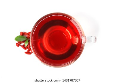 Healthy goji tea in glass cup with berries on white background, top view