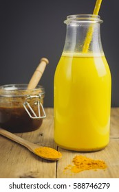 Healthy golden milk in a bottle and honey in a jar