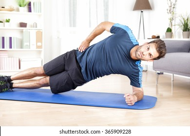 Healthy Gorgeous Man Doing an Indoor Side Plank Exercise on a Mat While Looking at the Camera.