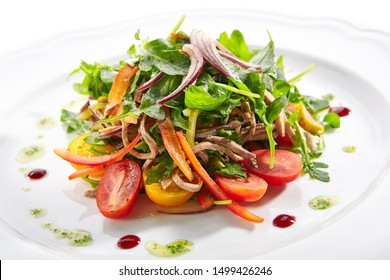 Healthy gourmet salad with sliced beef tongue, arugula, paprika, tomatoes and dressing a la pesto on white plate background. Delicious lunch menu with fresh meat and vegetable salat closeup