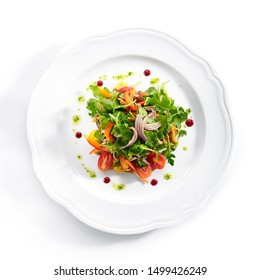 Healthy gourmet salad with sliced beef tongue, arugula, paprika, tomatoes and dressing a la pesto on white plate background. Delicious lunch menu with fresh meat and vegetable salat topview